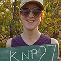 Sarah Hueber, Biology Alum, holds a location sign used for learning about and protecting wild Lions.