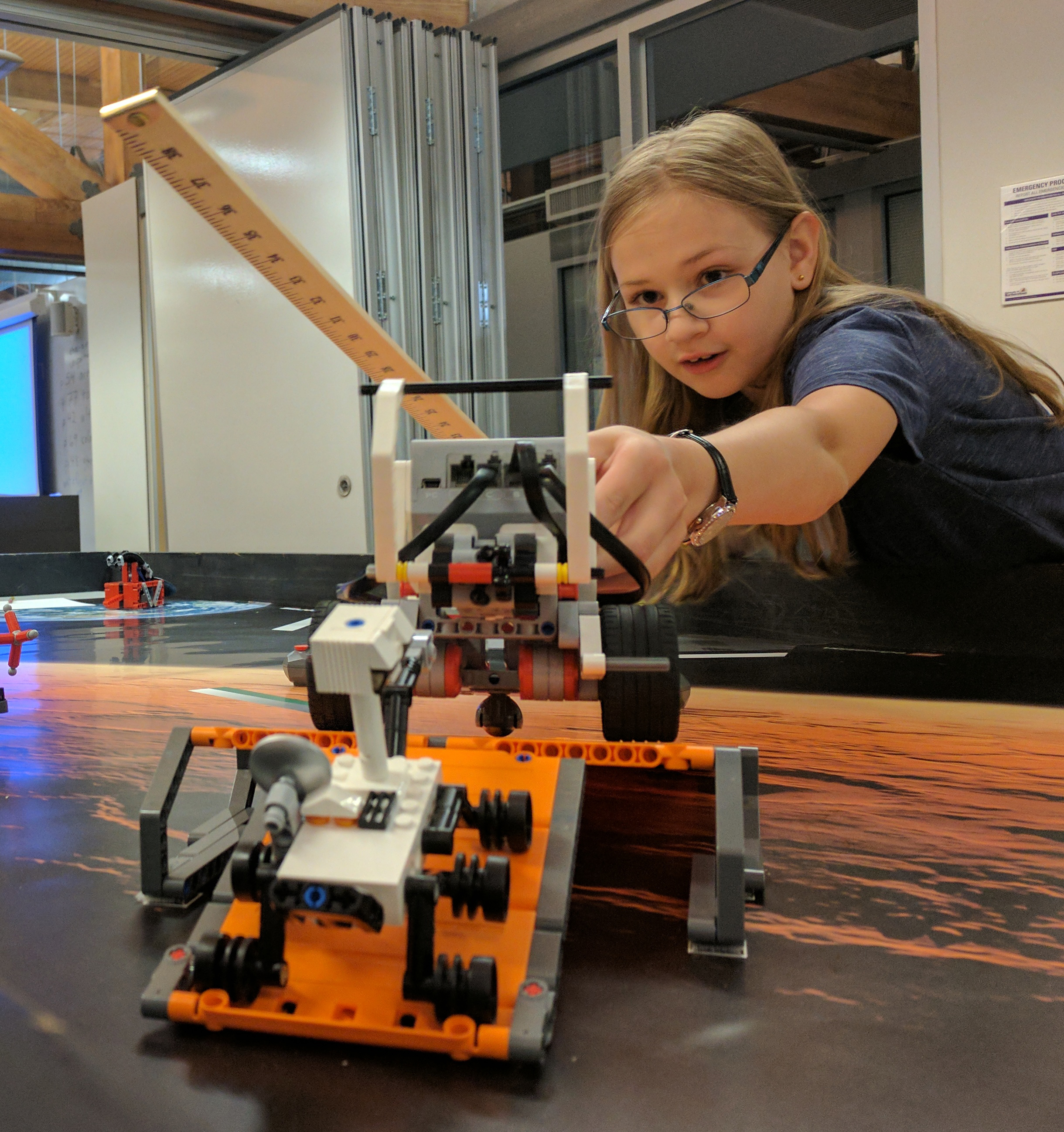 2017 Introduction to Robotics Camper measuring the field so that she can improve her program and the accuracy of her robot.