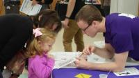 UNI STEM Ambassador with festival participant doscovering the answer to the case of the missing mascot.