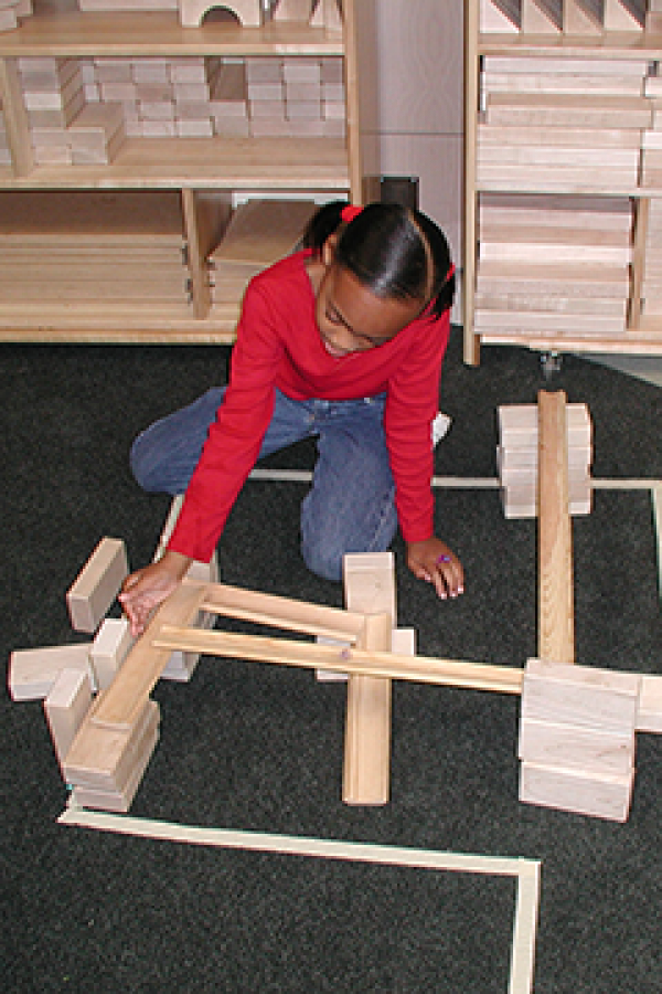 A young student explores forces and motion with Ramps and Pathways materials.