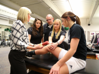 Dr. Tricia Schrage giving Athletic Training students hands on experience and education.