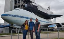 Tori Wills, Tyler Brown, and Dr. Ronald Rinehart in front of Shuttle Bay 2